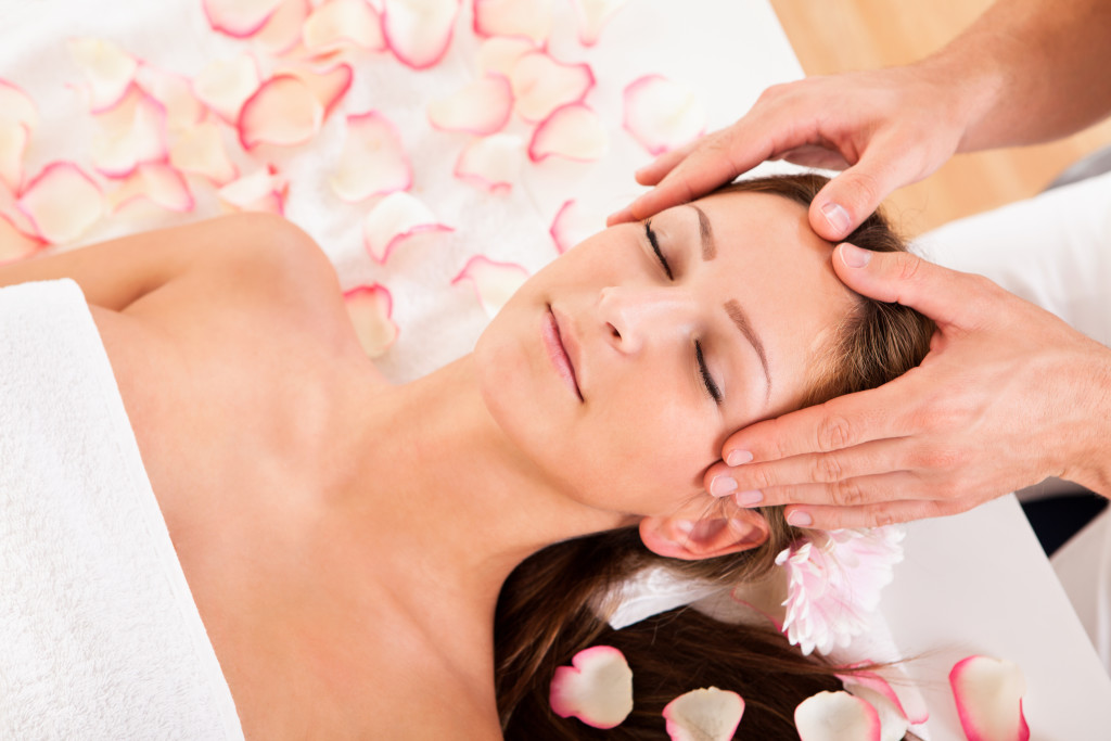 Beautiful woman with a flower in her hair enjoying a spa treatment smiling as a beautician gently massages her temples