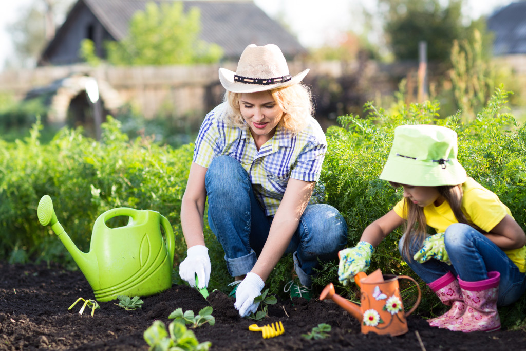mother and little daughter planting vegetable in home garden field
