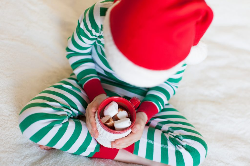 close-up of little boy in cozy pajamas holding cup with hot cocoa enjoying christmas time at home, shallow DOF